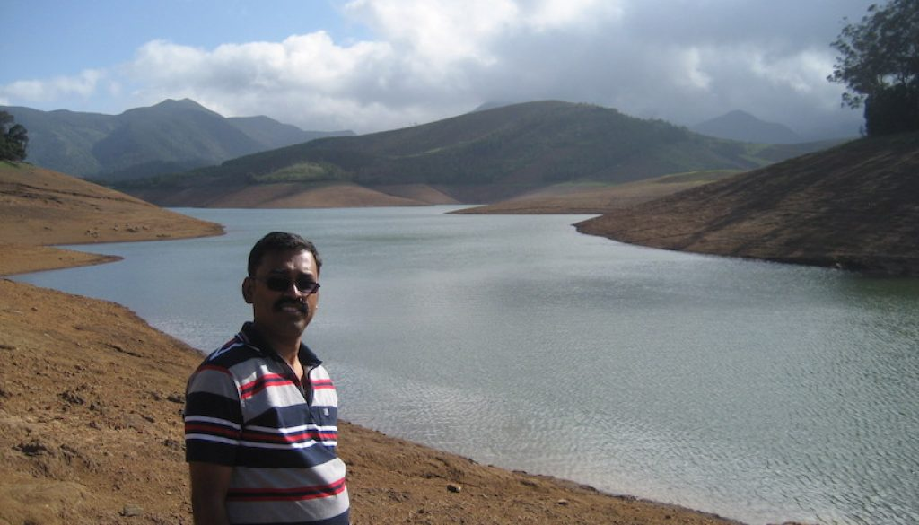 Man standing in front of Avalanche Lake, Ooty